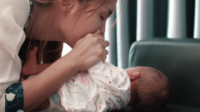 vidéos et rushes de mère embrassant peu bébés pieds - fête de naissance