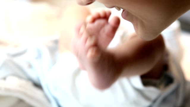Mother kissing little babies feet.FULL HD video