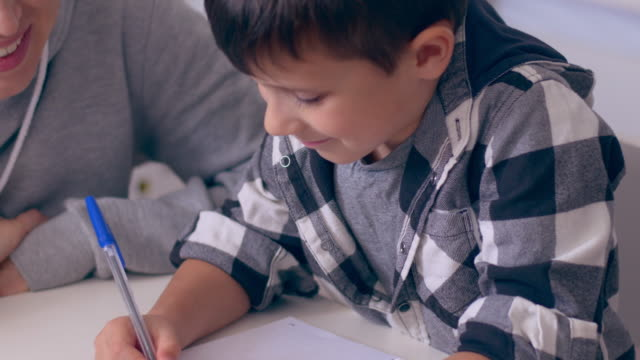 Mother learning son to write out a number in copybook video