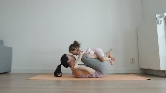 ヨガ: 母は、ホームサイドビューで彼女の足に小さな娘とヨガマットに横たわっています - 娘点の映像素材/bロール