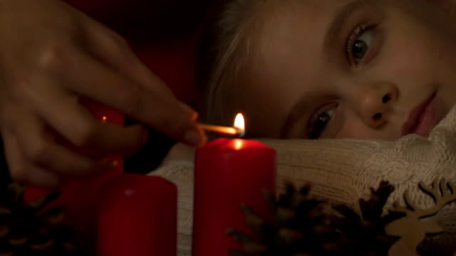 Mother lighting candles, daughter looking excitedly, happy holidays together video