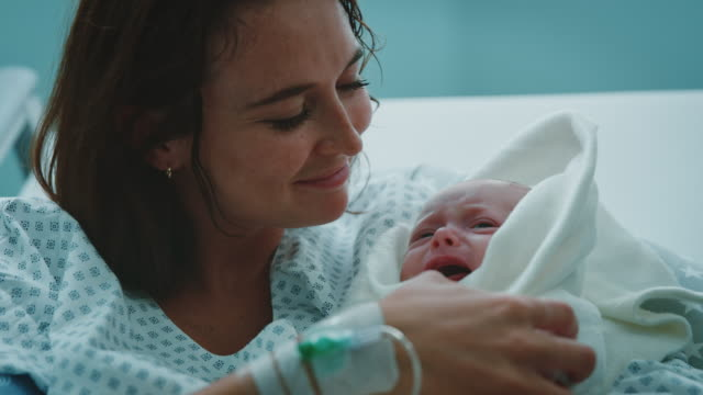 Mother looking at infant crying on bed in hospital