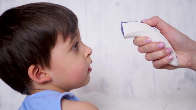 mère mesure la température d'un enfant garçon avec un dispositif sans contact - Vidéo