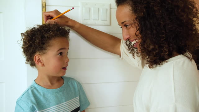 Mother Measuring Height of Son A mom measures her son against a ruler and wall to see how tall he is inside their home. The boy is growing fast at 4 years old and is excited to grow and learn with his mom teaching him. instrument of measurement stock videos & royalty-free footage