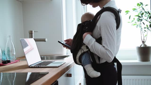 mamma multitasking med hjälp av telefon och laptop medan du håller baby i bärsele - working from home bildbanksvideor och videomaterial från bakom kulisserna
