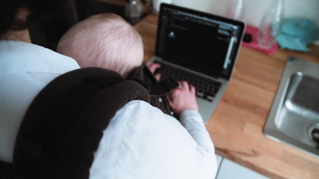 mamma multitasking med baby i sling och använda laptop - working from home bildbanksvideor och videomaterial från bakom kulisserna