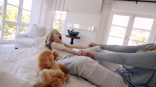 mother on bed playing with her daughter - fare il solletico video stock e b–roll