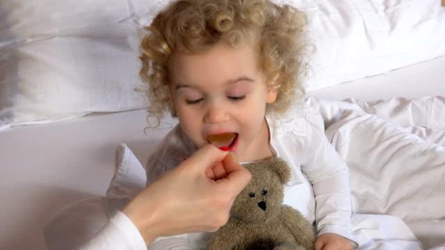 мать или врач дают счастливый малыш девушка ложка с витамином медицины - сироп стоковые видео и кадры b-roll