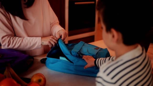 子供用ランチ ボックスでスクール バッグを梱包の母 - 荷造り点の映像素材/bロール