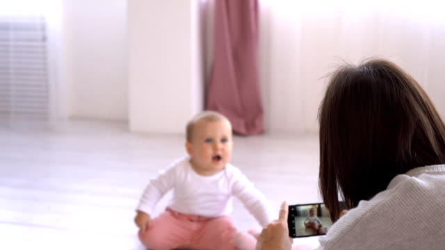 mother photographing playful baby girl using mobile phone camera - fotografare video stock e b–roll