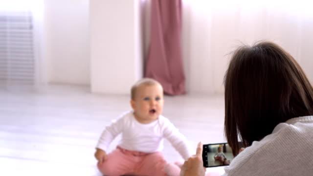 母親用手機相機拍攝好玩的女嬰 - 摄影 個影片檔及 b 捲影像