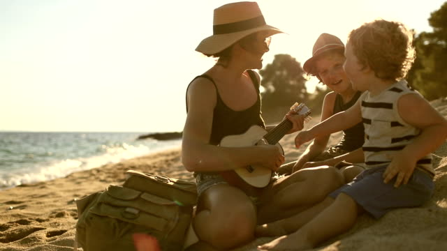 Mother Playing a guitar with her boys at the beach video