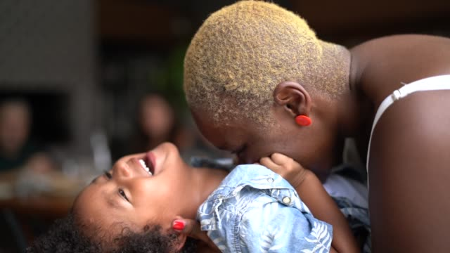vídeos de stock e filmes b-roll de mother playing and kissing her son - afro
