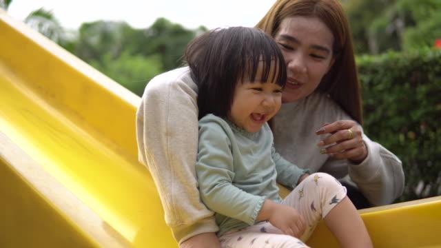 母親玩滑塊與女兒在操場上 - 休閒器具 個影片檔及 b 捲影像