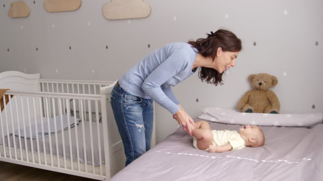 Mother Playing With Baby Son Lying On Bed In Nursery video