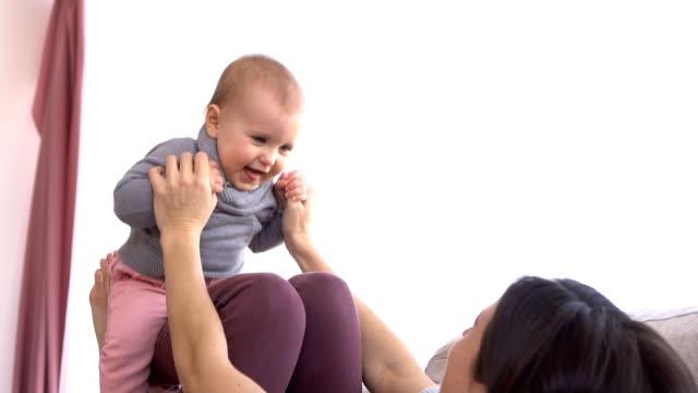 母が元気な女児を自宅で遊ぶ - 持ち上げる点の映像素材/bロール