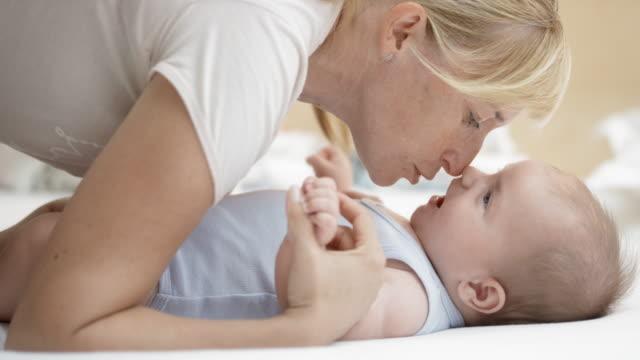 vidéos et rushes de mère jouant avec son petit garçon sur le changeur - 0 11 mois