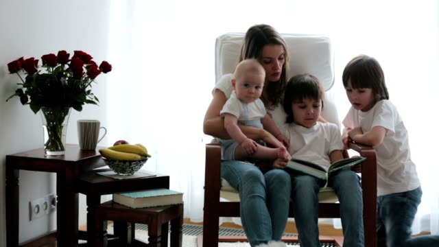 Mother, playing with her toddler boy and his older brothers, reading book