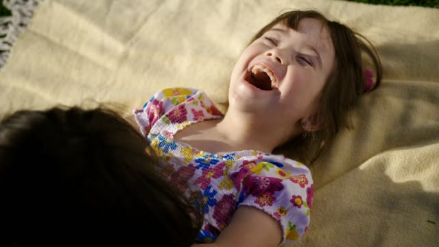 mother playing with little laughing daughter - fare il solletico video stock e b–roll