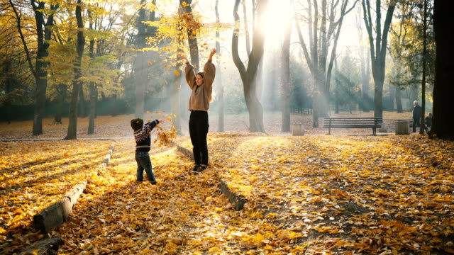 Mother playing with little son in park in autumn