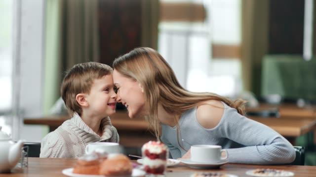 mamma leker med sonen som rör näsor och har kul på caféet. medium närbild skott på 4k röd kamera - brownie bildbanksvideor och videomaterial från bakom kulisserna