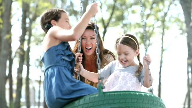 Mother playing with two girls at park, on tire swing video