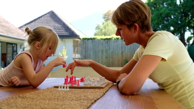 Mother plays a game of chess with her daughter