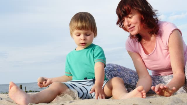 mother plays with little child on beach - eastern european descent stock videos & royalty-free footage