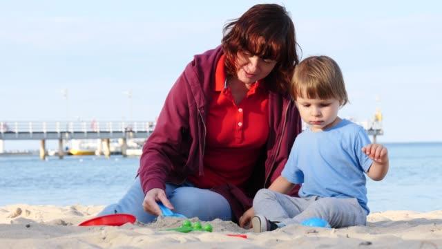 mother plays with little child on beach - wschodnio europejski filmów i materiałów b-roll