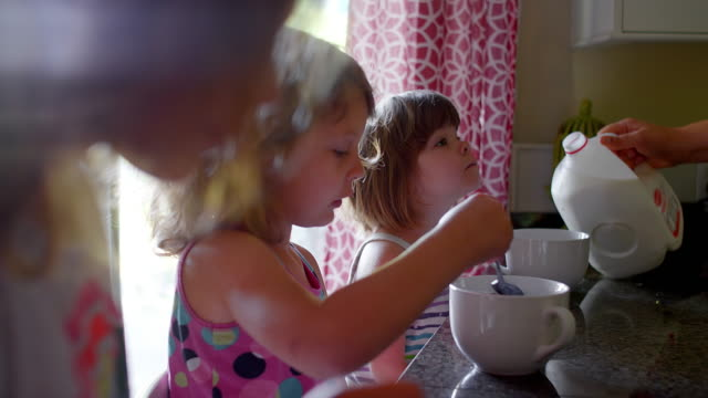 A mother pours milk into her daughters' cereal bowls video