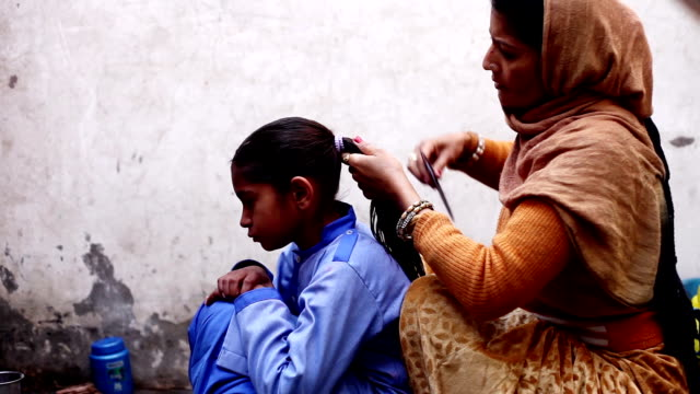 Mother preparing little girl for school HD1080p: Mother preparing her daughter for going school. indian family stock videos & royalty-free footage