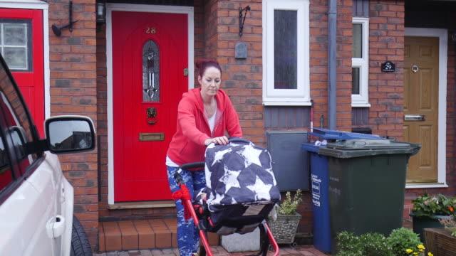 mor förberedelser att köra med hennes baby utomhus - cold street bildbanksvideor och videomaterial från bakom kulisserna