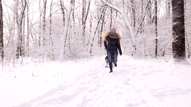 Mother pulling son on sledge in a winter forest. video