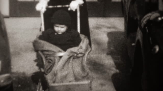 1941: Mother pushing baby stroller wearing black funny tiny fashion hat. video