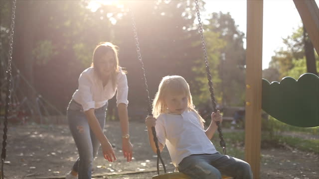 Mother pushing child on a swing set. Slow motion video