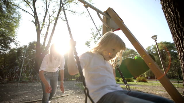mütter schieben kind auf schaukel - kind schaukel stock-videos und b-roll-filmmaterial