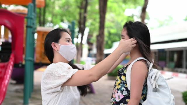 母親在女兒臉上戴上安全口罩,用於保護covid-19或村公園爆發冠狀病毒,準備上學。回到學校的概念。預防冠狀病毒的醫學口罩。 - back to school 個影片檔及 b 捲影像