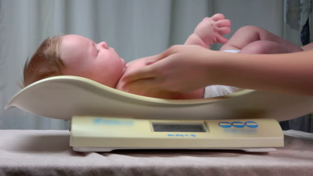 Mother puts the baby on the scales video