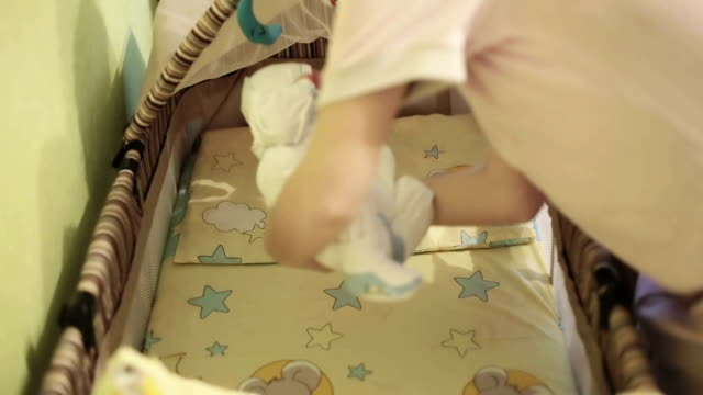 Mother puts the newborn baby in the a cot and covered with a blanket. video