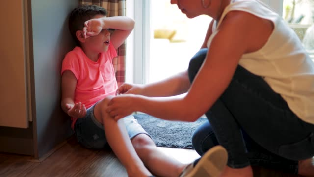 mother putting band aid on childs knee - rana filmów i materiałów b-roll