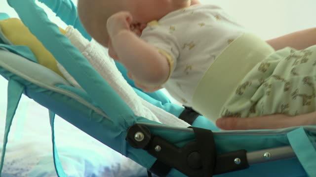 cu mother putting crying baby boy (2-5 months) in seat / vrhnika, slovenia - negativ bildart stock-videos und b-roll-filmmaterial