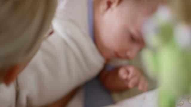 vídeos de stock, filmes e b-roll de mãe colocando seu filho bebê para dormir - mobile