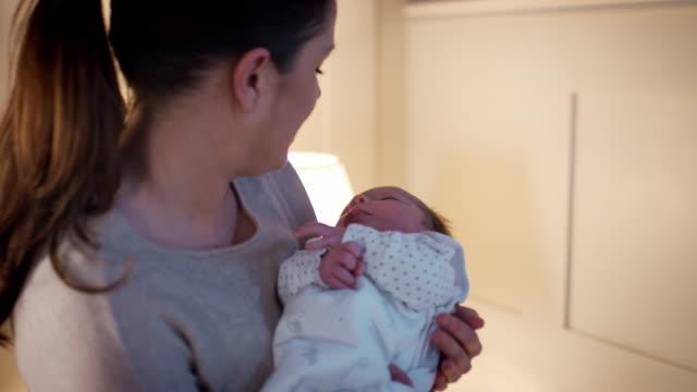 mor sätta nyfödda son till barnsäng för sömn - baby sleeping bildbanksvideor och videomaterial från bakom kulisserna