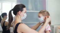 istock Mother Putting on a Medical Mask on her Child 1214245876