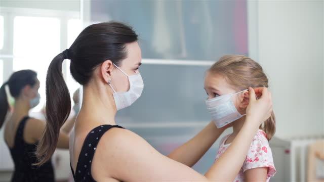 vidéos et rushes de mère mettant sur un masque médical sur son enfant - enfant masque