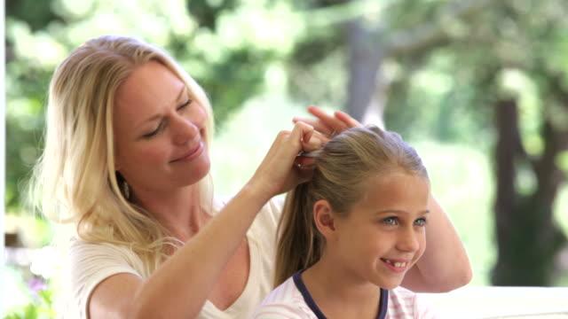 stockvideo's en b-roll-footage met mother putting ponytail in daughters hair - paardenstaart haar naar achteren