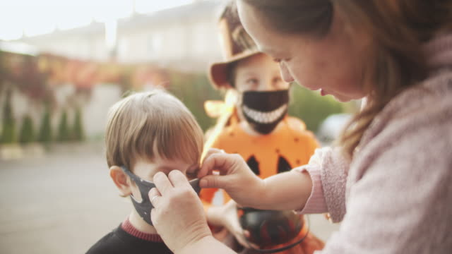 vídeos de stock e filmes b-roll de mother putting protective face mask on her child during covid-19 pandemic on halloween - halloween