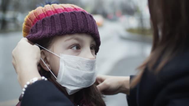 mother putting protective face mask on her child - nakładać filmów i materiałów b-roll