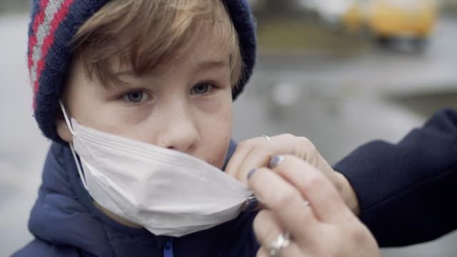 vidéos et rushes de mère mettant le masque protecteur de visage sur son enfant - enfant masque