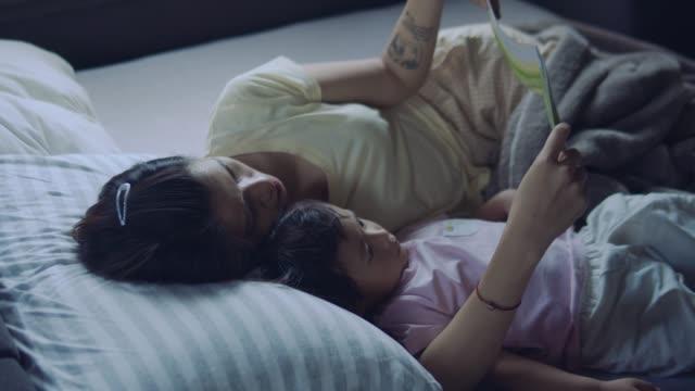 mor, läsa en bok till sin son på morgonen i sängen hemma - cosy pillows mother child bildbanksvideor och videomaterial från bakom kulisserna